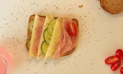 Tostada de jamón, queso, pepino y tomate.